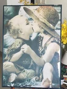 Kid's kissing poster inside the glass frame